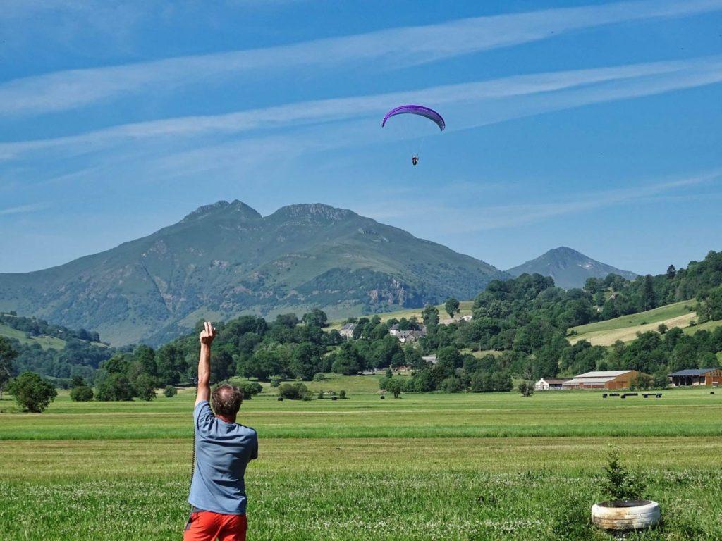 Guidage d'un stagiaire à l'atterrissage pendant un stage initiation parapente chez thang-ka, Cantal, Auvergne