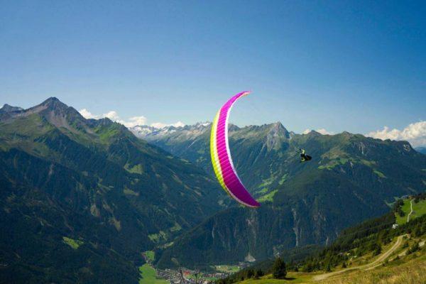 Une Rise 4 violette de chez Air Design en vol près du relief