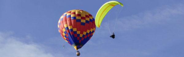 Une Mcc Aviation Explora en vol devant une montgolfière.