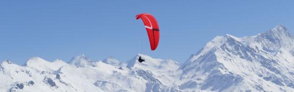 Une Mcc Aviation Stelvia rouge en cross avec de belles montagnes enneigées au fond.