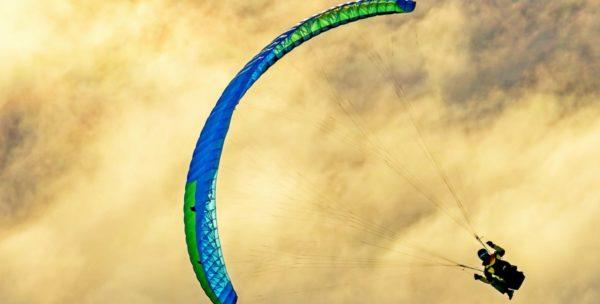 La Niviuk Skin 3 P bleue en vol devant un nuage jaune doré en fin de journée.