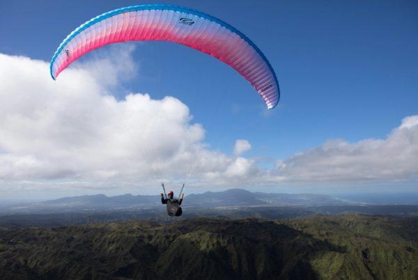 Une Ozone Swift 5 bleu blanche et rose en vol face à nous