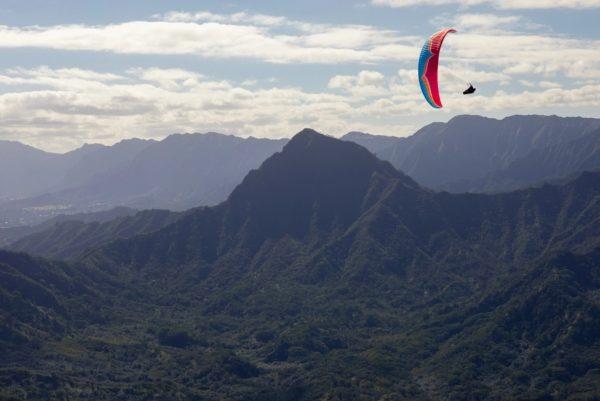 Une Ozone Swift 5 en vol montagne qui enroule sur la tranche
