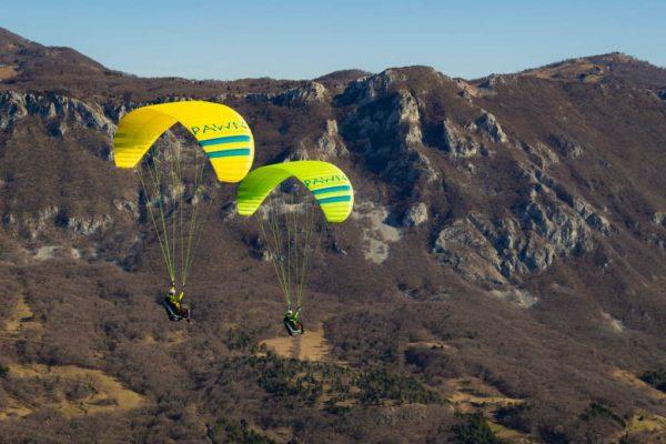 Deux Triple Seven Pawn-Evo jaune et verte en vol en montagne
